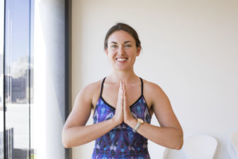 Meagan smiles while putting her hands together in namaste.