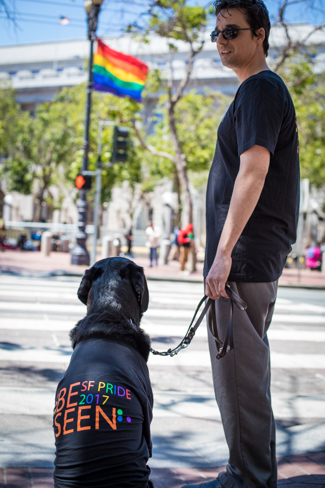 Ethan and his guide dog Gershwin show off their LightHouse Pride t-shirts across from the UN Plaza, with a rainbow flag billowing in the background.