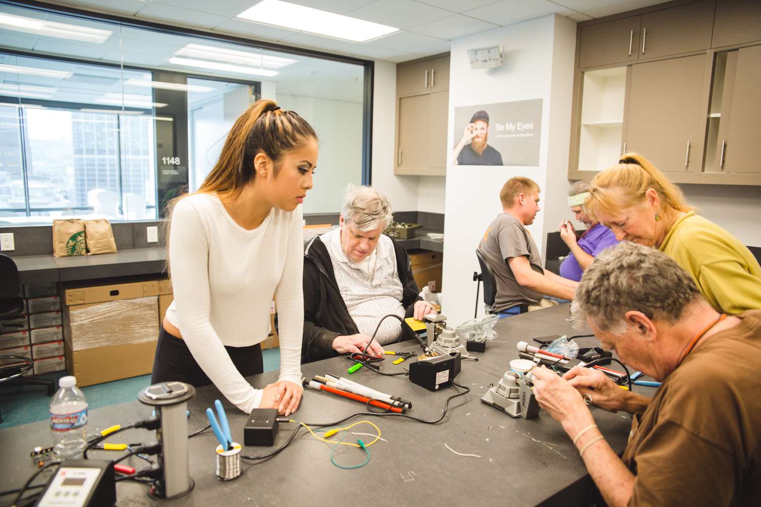 Six students and volunteers sit around two tables, hard at work. The grey work surface is scattered with castaway bits of wire and solder. The lab's large windows offer a view of neighboring grey buildings.