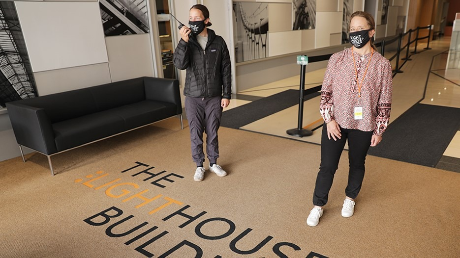 Two people wearing masks standing six feet apart in the LightHouse building lobby at 1155 Market Street