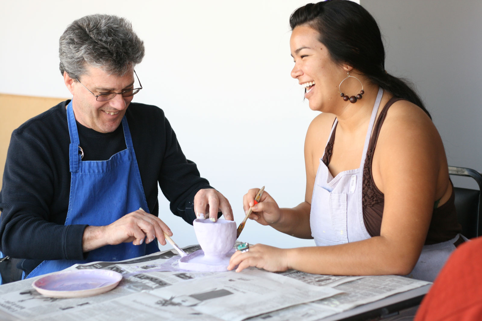 Two LightHouse studios smile as they work on a pottery project